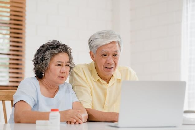 Casal de idosos asiáticos usando conferência portátil com médico sobre medicina informação na sala de estar Foto gratuita