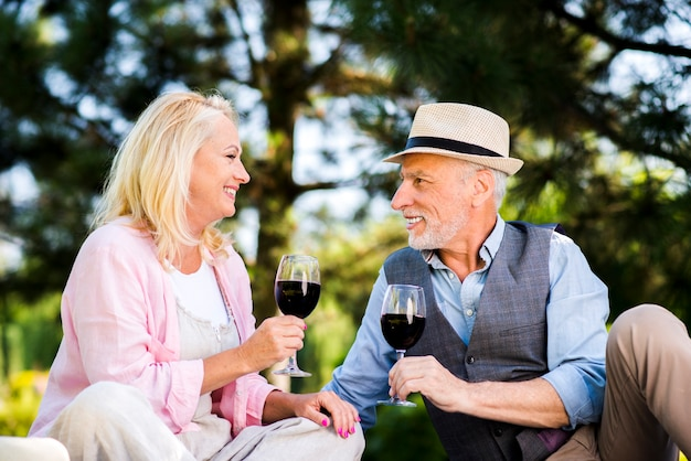 Casal de idosos com taças de vinho na natureza Foto gratuita