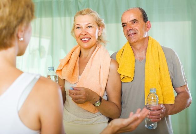 Casal de idosos conversando com treinador Foto gratuita