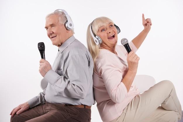 Casal de idosos em fones de ouvido está cantando karaoke. Foto Premium