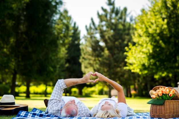 Casal de idosos fazendo coração com as mãos Foto gratuita