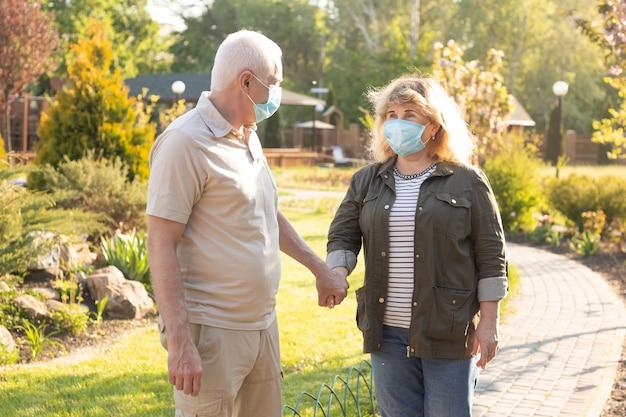 Casal de idosos idosos felizes usando máscara médica para proteger de coronavírus no parque de verão Foto Premium