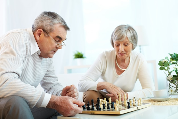 Casal de idosos jogando xadrez em casa Foto gratuita