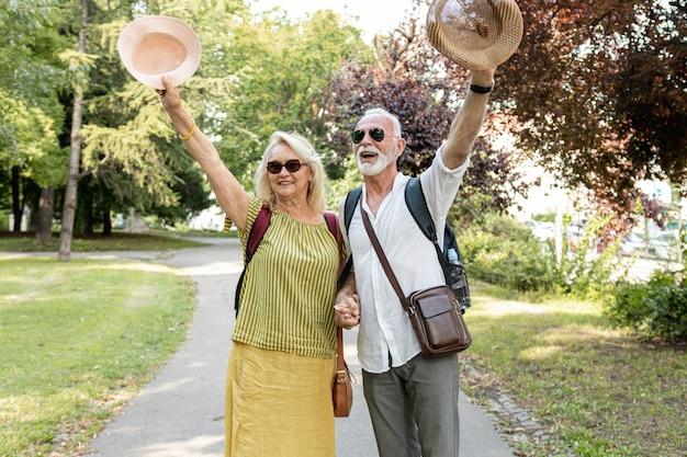 Casal de idosos levantando seus chapéus no ar Foto gratuita