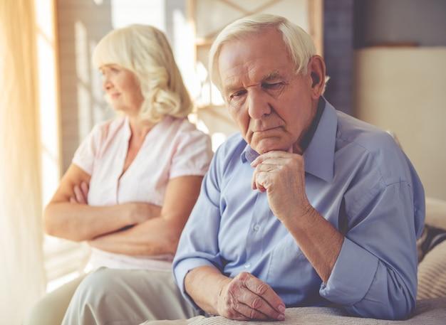 Casal de idosos pensativo está sentado no sofá Foto Premium