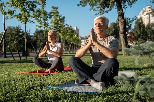 Casal de idosos praticando ioga ao ar livre Foto gratuita