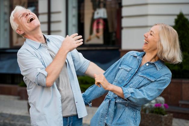 Casal de idosos rindo e aproveitando o tempo ao ar livre na cidade Foto gratuita