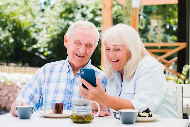 Casal de idosos rindo olhando para smartphone Foto gratuita
