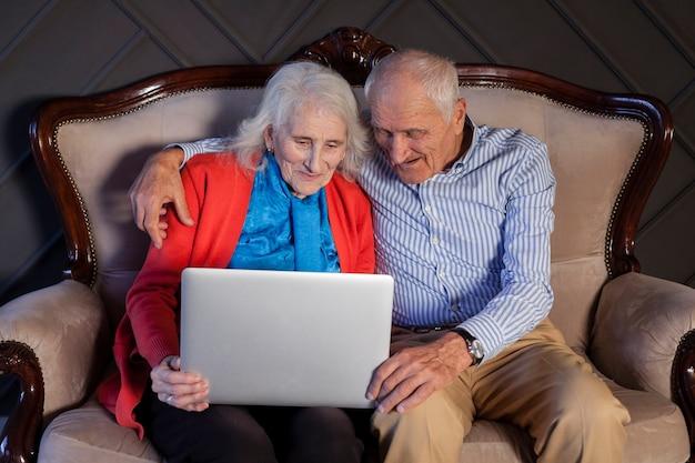 Casal de idosos segurando um laptop juntos Foto gratuita