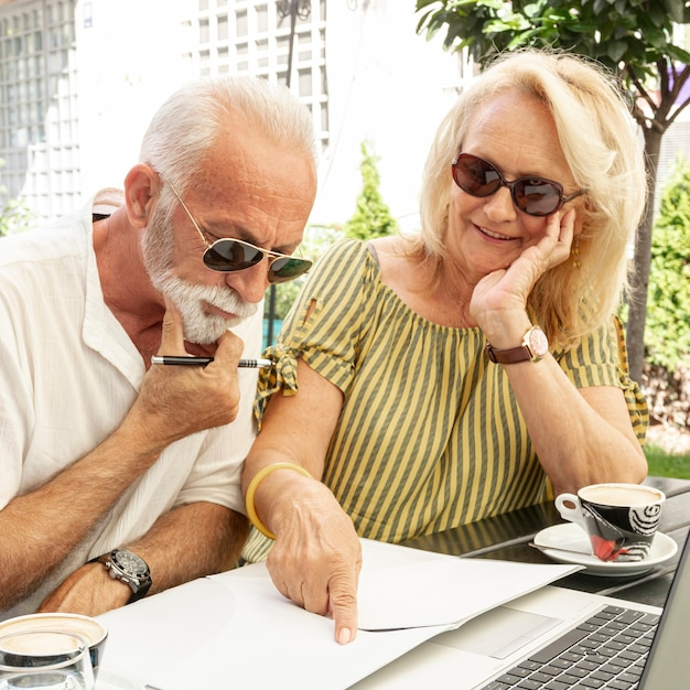 Casal de idosos tomando notas na agenda Foto gratuita