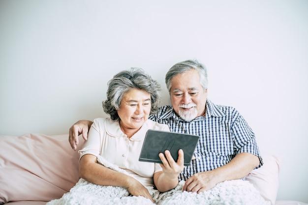 Casal de idosos usando computador tablet Foto gratuita