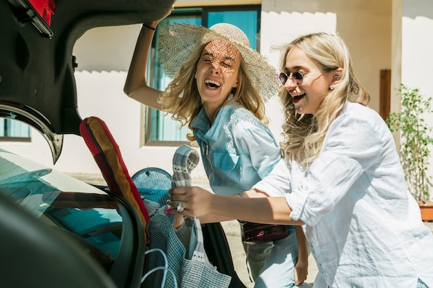 Casal de jovens lésbicas se preparando para uma viagem de férias no carro em um dia ensolarado. meninas sorridentes e felizes antes de ir para o mar ou oceano. conceito de relacionamento, amor, verão, fim de semana, lua de mel, férias. Foto gratuita