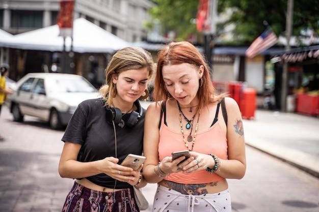 This image has an empty alt attribute; its file name is casal-de-jovens-mulheres-olhando-para-o-celular-na-rua_138670-609.jpg