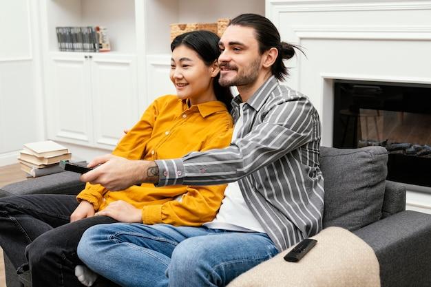 Casal de lado sentado no sofá assistindo tv Foto gratuita