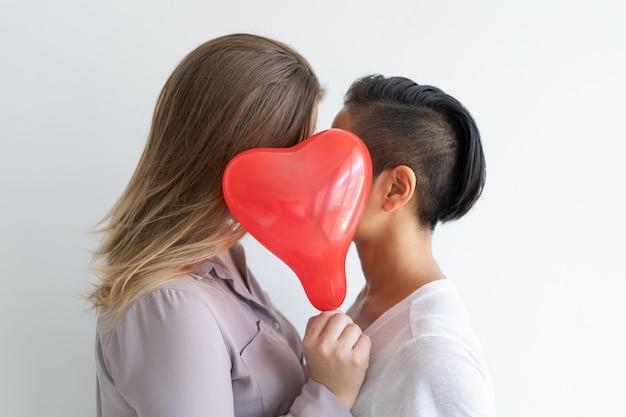 Casal de lésbicas beijando atrás de balão em forma de coração Foto gratuita