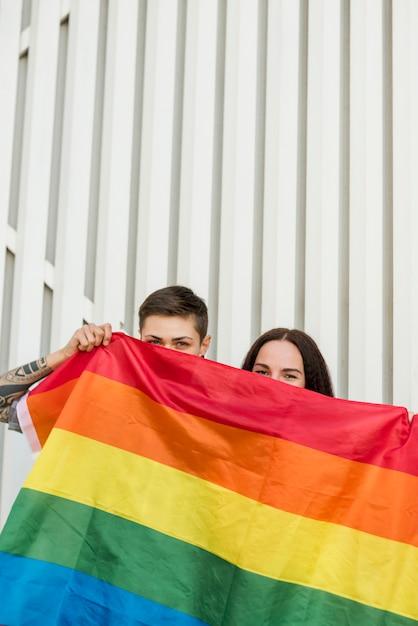 Casal de lésbicas se escondendo atrás de bandeira lgbt Foto gratuita