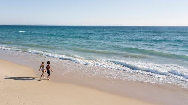 Casal de mãos dadas e indo para o mar Foto gratuita