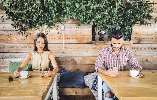 Casal de moda no momento de desinteresse ignorando um ao outro usando telefone celular móvel Foto Premium
