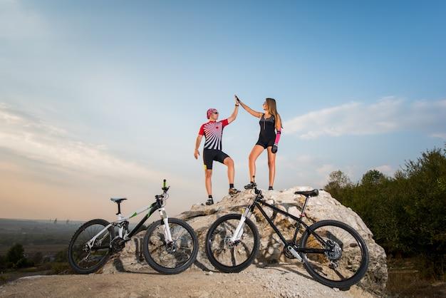 Casal de motoqueiros em pé sobre uma rocha perto de bicicletas e dando mais cinco contra o céu azul Foto Premium