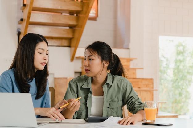Casal de mulheres asiáticas lgbtq lésbicas de negócios conta em casa Foto gratuita