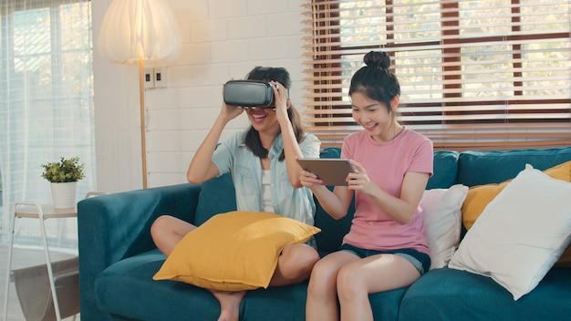 Casal de mulheres asiáticas lgbtq lésbicas jovens usando tablet em casa Foto gratuita