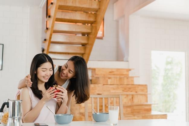 Casal de mulheres lésbicas asiáticas lgbtq dando casa presente Foto gratuita