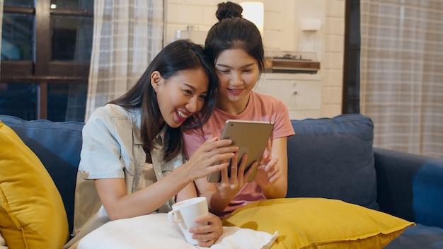 Casal de mulheres lésbicas lgbt usando tablet em casa Foto gratuita