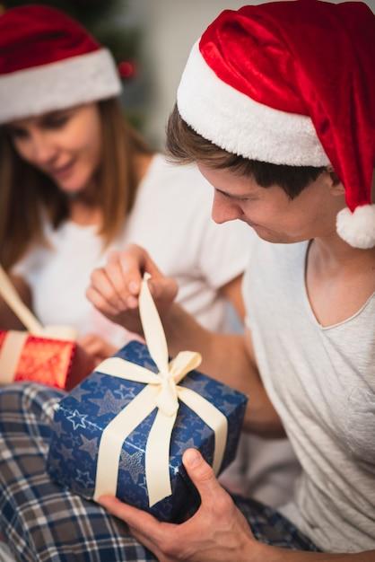 Casal de natal abrindo presentes Foto gratuita
