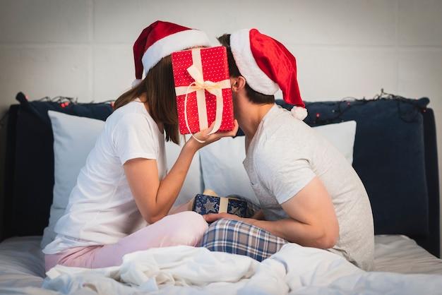 Casal de natal se escondendo atrás de presente Foto gratuita