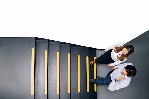 Casal de negócios jovem nas escadas no escritório Foto Premium