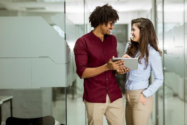 Casal de negócios multiétnico usando um tablet digital no escritório Foto Premium