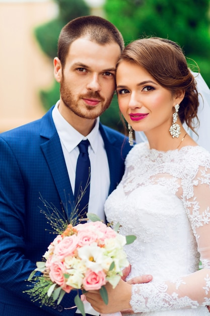 Casal de noivos apaixonados, beijando e sorrindo. jovem noiva muito elegante e seu noivo bonito posando no parque verde. Foto gratuita