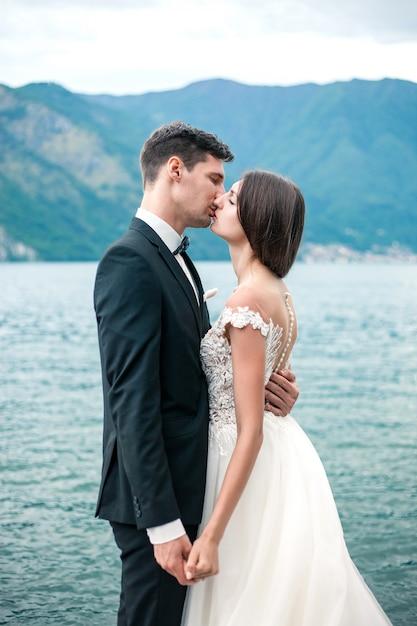 Casal de noivos beijando no fundo de um lago e montanhas Foto Premium