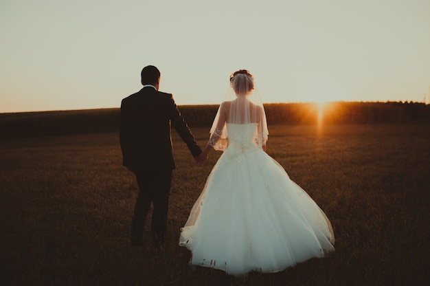 Casal de noivos com o pôr do sol Foto Premium