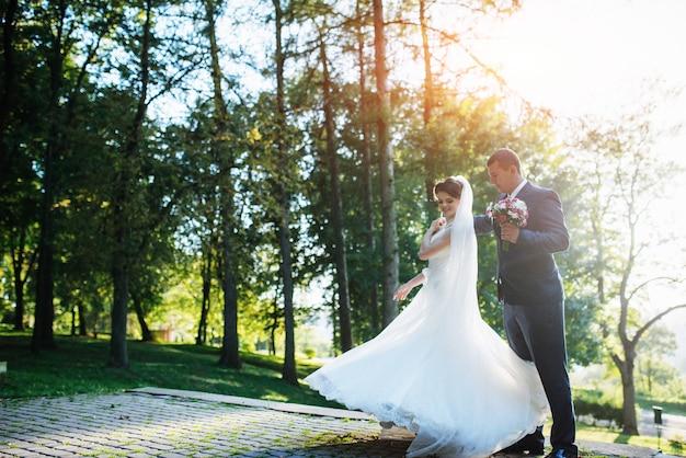 Casal de noivos dançando no parque Foto Premium
