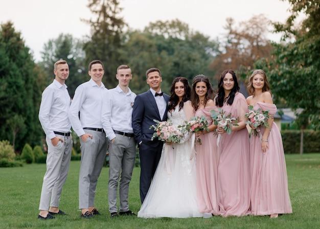 Casal de noivos e melhores amigas vestidas com trajes de casamento na moda estão na fila no quintal verde Foto gratuita