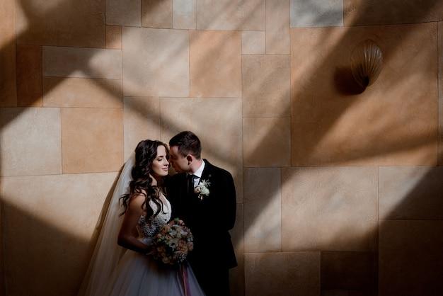 Casal de noivos está de pé perto da parede em raios de sol e quase se beijando, conceito de casamento Foto gratuita