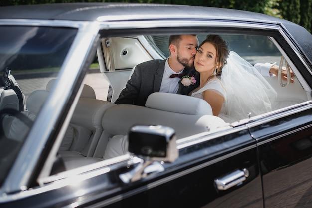 Casal de noivos estão sentados no banco de trás de um carro e beijando Foto gratuita