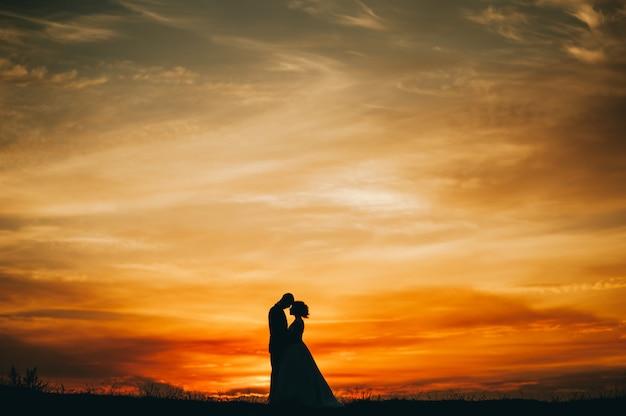 Casal de noivos no fundo do pôr do sol Foto Premium