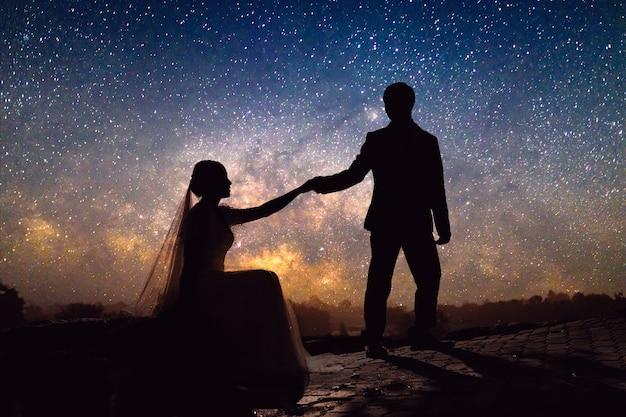 Casal de noivos românticos de silhueta segurando a mão na colina de grama na via láctea com campo de estrelas Foto Premium