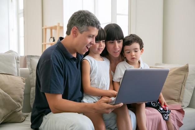 Casal de pais alegres e animados segurando os filhos no colo, sentados no sofá todos juntos, assistindo a um filme ou vídeo no laptop em casa, olhando para a tela. Foto gratuita