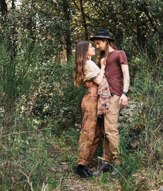 Casal de pedestrianismo apaixonado beijando na natureza Foto gratuita