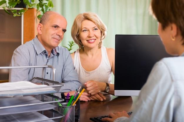 Casal de pensionistas conversando com o empregado Foto gratuita