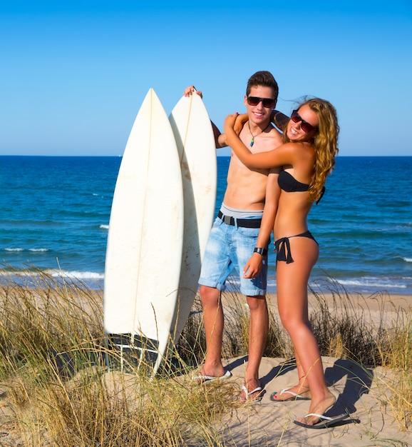 Casal de surfistas adolescentes abraço na praia Foto Premium