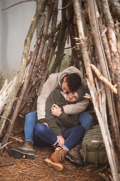 Casal de tiro completo abraçando no abrigo Foto gratuita