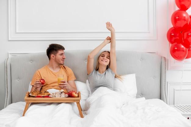 Casal de tiro médio com café da manhã e balões no quarto Foto gratuita