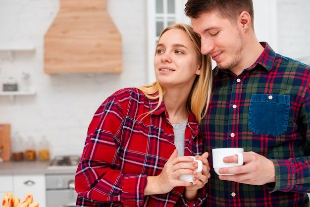 Casal de tiro médio na cozinha com copos de café Foto gratuita