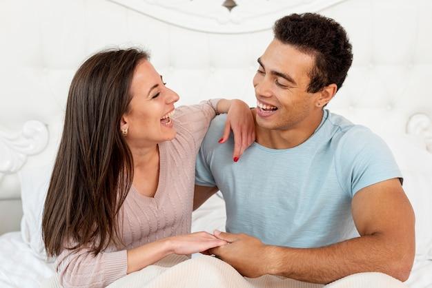 Casal de tiro médio rindo juntos Foto gratuita