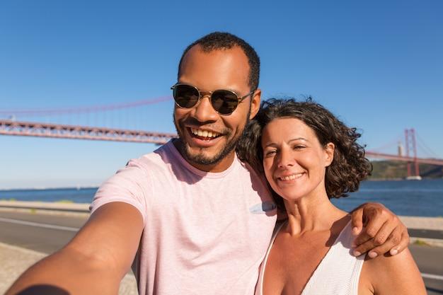 Casal de turistas alegres tomando selfie no passeio da cidade Foto gratuita