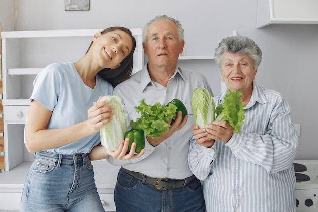 Casal de velhos em uma cozinha com jovem neta Foto gratuita